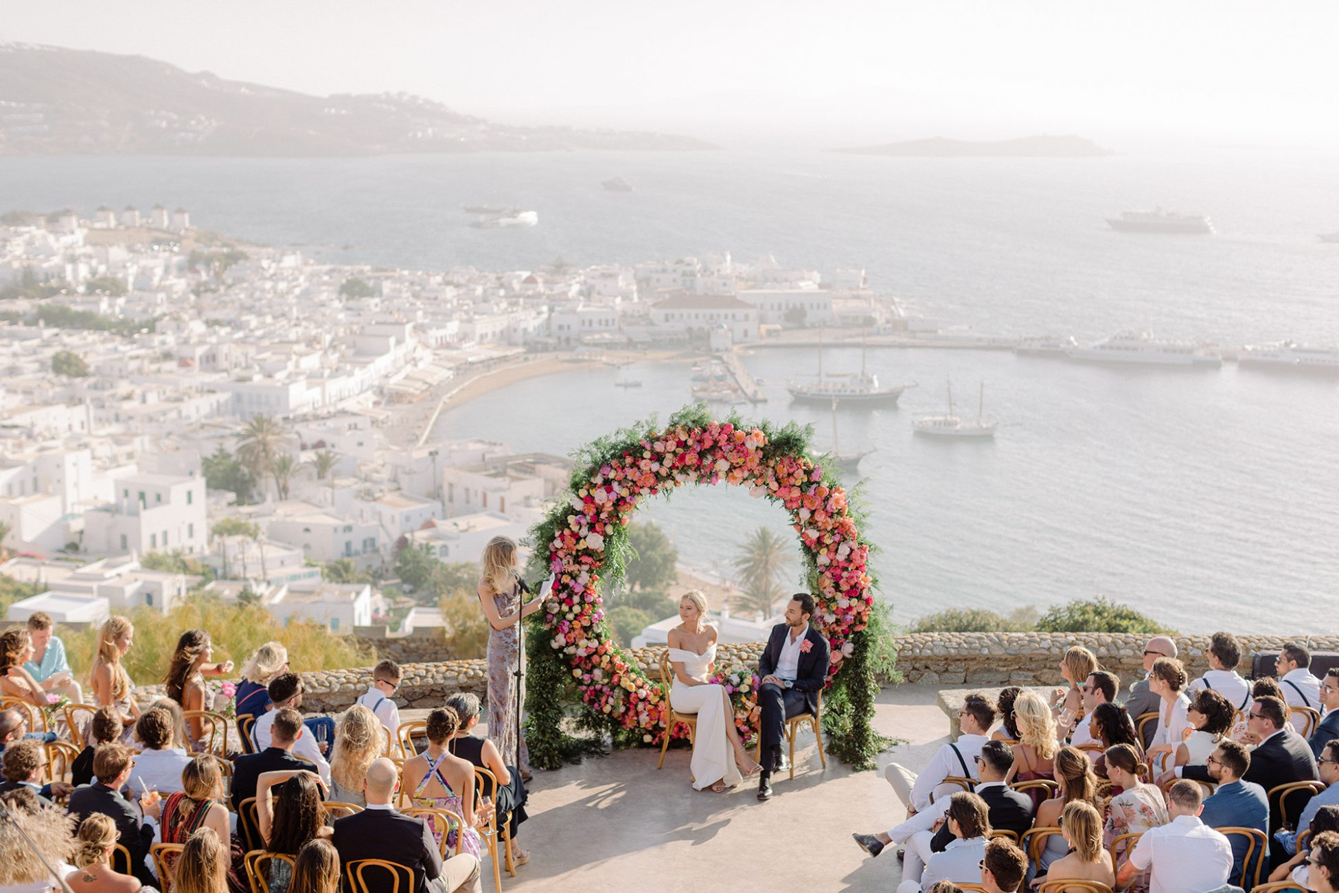Panoramic image of a wedding is Mykonos 180 Sunset overlooking the Mykonian Chora and port