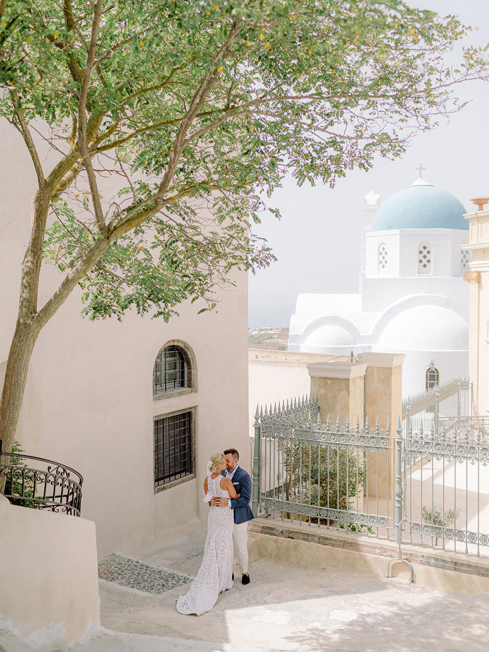 santorini wedding couple hugging blue dome in the background