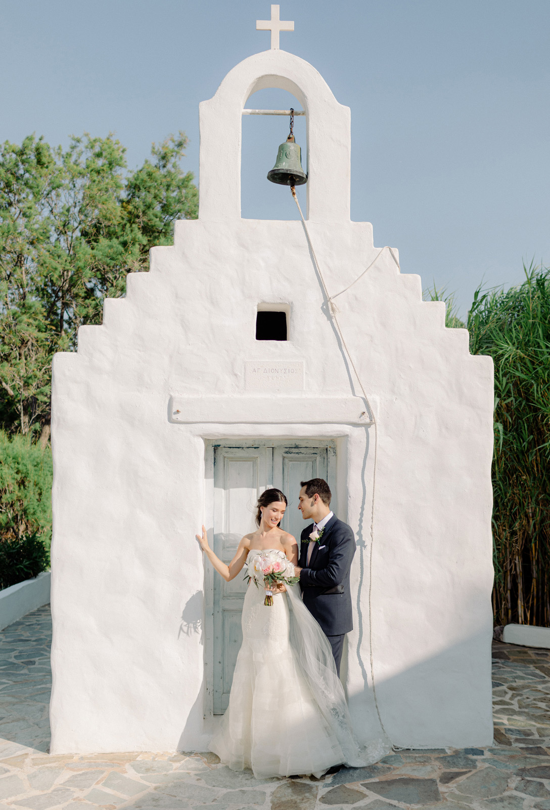 Athens wedding photographer captures couple in front of white washed chapel hugging
