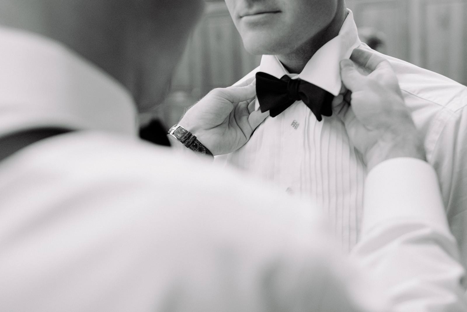 Dallas wedding best man helps groom tie his bowtie
