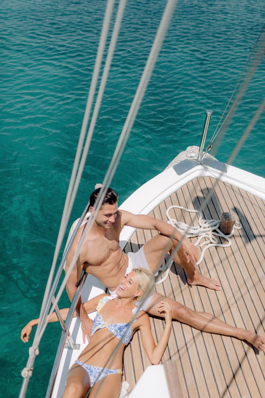 Engagement photographer in Greece captures couple sunbathing on the deck of a sailboat