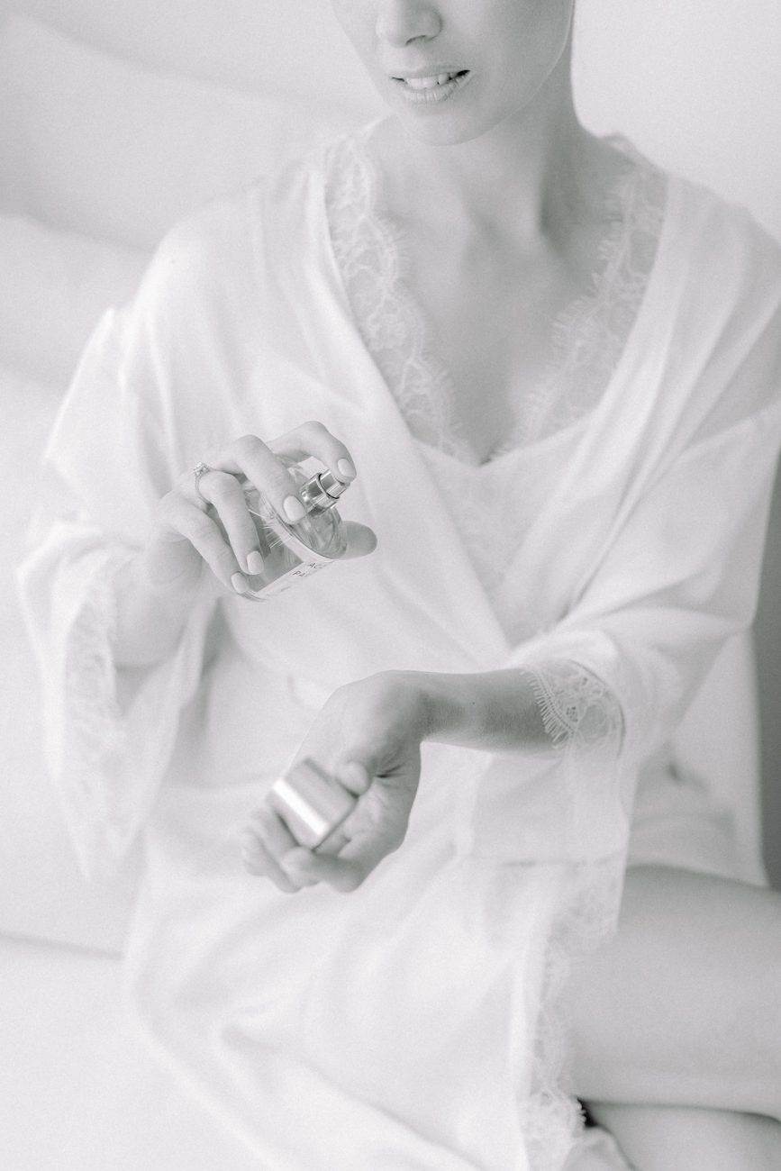 Mykonos bride spraying perfume on her wrist at t her wedding preparation