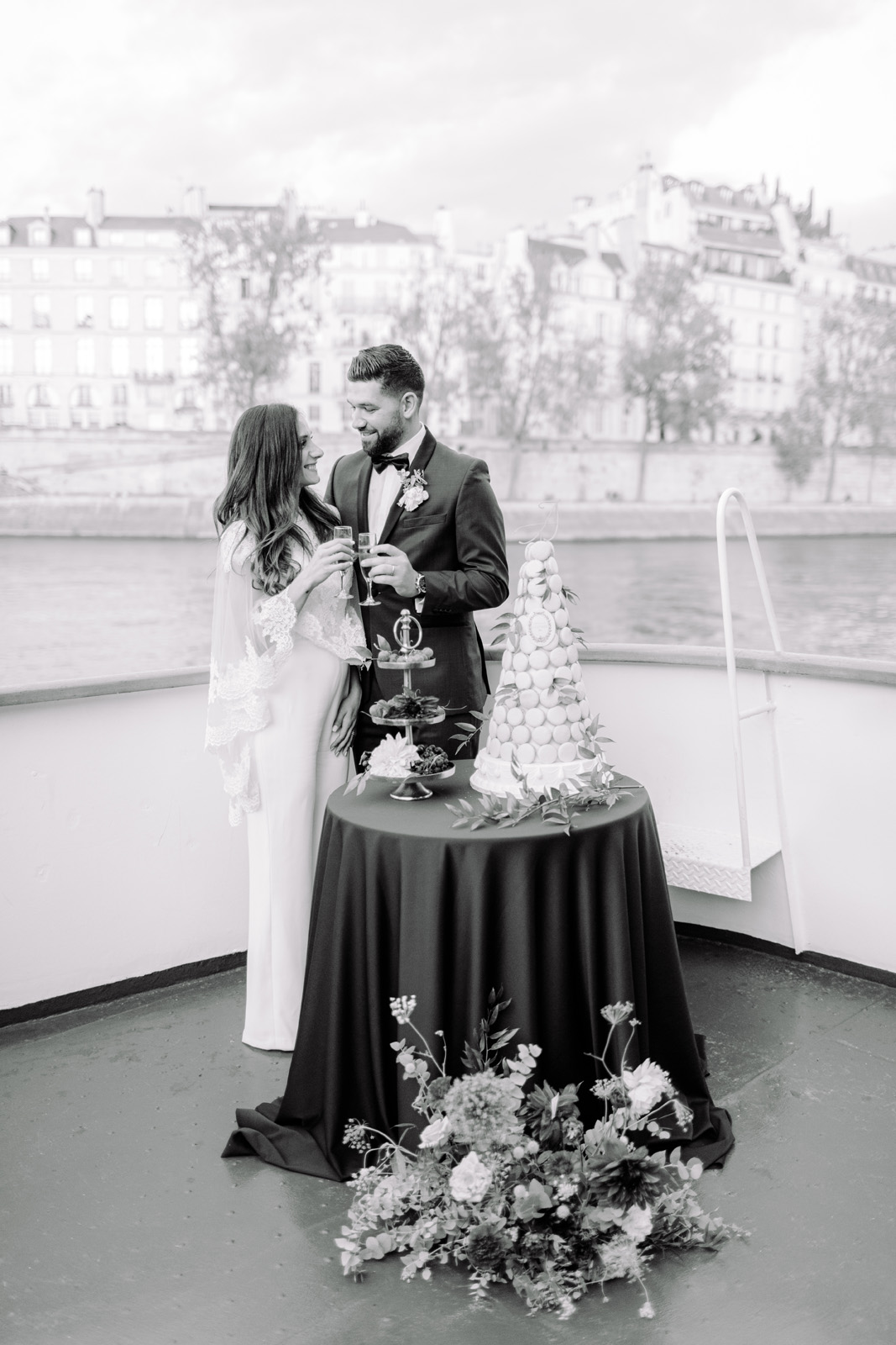 Paris wedding photographer captures couple cutting cake on a private boat on river Seine